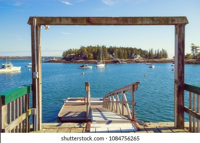 GEORGETOWN, MAINE - OCTOBER 14, 2017: A view from a fishing dock overlooking numerous boats moored in blue waters of picturesque Sheepscot Bay.