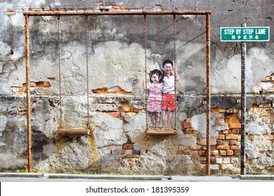 "GEORGETOWN, MALAYSIA - JANUARY 19, 2014: Street Art by Louis Gan ""Brother and sister on a swing"". It graces the wall of the Printing Warehouse in an alleyway Chulia Street Ghaut, Step By Step Lane."