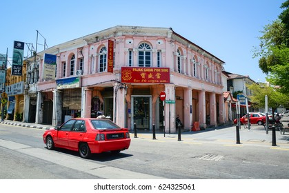 Georgetown, Malaysia - Mar 10, 2016. A red car runs on street in George Town, Malaysia. One of the oldest cities in Malaysia, George Town was inscribed as a UNESCO in 2008.