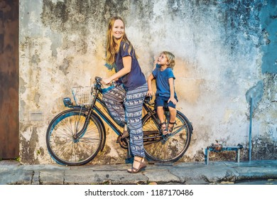 Georgetown, Penang, Malaysia - April 20, 2018: Mother and son on a bicycle. Public street art Name Children on a bicycle painted 3D on the wall that's two little Chinese girls riding bicycle in