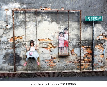 "Georgetown, Penang, Malaysia - April 23: Asian girl posing for a photo with street art piece ""Children on the Swing"" by local artist Louis Gan in George Town, Penang, Malaysia."