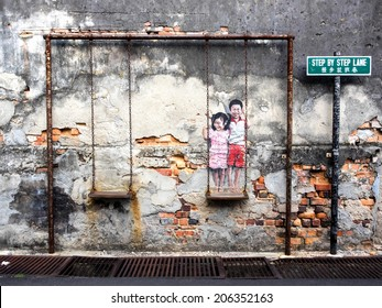 "Georgetown, Penang, Malaysia - April 23: ""Children on the Swing"" street art piece by local artist Louis Gan in George Town, Penang, Malaysia."