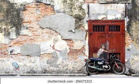 """Georgetown, Penang, Malaysia - April 23: Street art mural  """"Little Boy With Pet Dinosaur"""" and """"Boy on a Bike"""" by Lithuanian artist Ernest Zacharevic in George Town, Penang, Malaysia."""