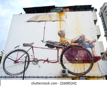 """Georgetown, Penang, Malaysia - April 23: """"The Awaiting Trishaw Paddler"""" street art mural painted by Lithuanian artist Ernest Zacharevic in George Town, Penang, Malaysia."""
