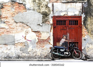"""Georgetown, Penang, Malaysia - April 23: Famous street art mural """"Boy on a Bike"""" by Ernest Zacharevic in George Town, Penang, Malaysia."""