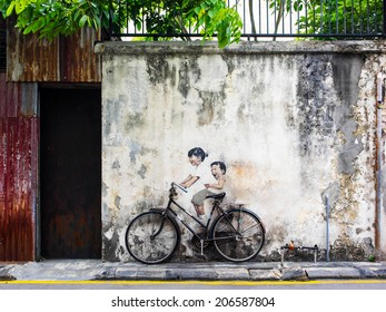 """Georgetown, Penang, Malaysia - April 24: """"Little Children on a Bicycle"""" street art mural by Lithuanian artist Ernest Zacharevic in George Town, Penang, Malaysia."""