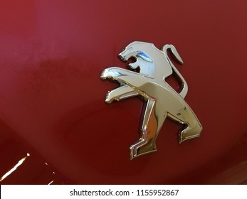 Georgetown, Penang, Malaysia. August 14, 2018. Emblem of the car brand of Peugeot isolated on red background of the car engine hood.