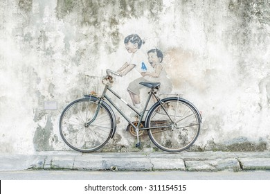 "Georgetown, Penang, Malaysia - August 2, 2015: ""Little Children on a Bicycle"" street art mural by Lithuanian artist Ernest Zacharevic in George Town, Penang, Malaysia."
