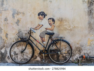 "Georgetown, Penang, Malaysia - August 23, 2013: Wall artwork named ""Little Children on a Bicycle"" in Penang Georgetown UNESCO heritage zone by Lithuanian artist Ernest Zacharevic"
