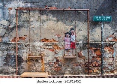 """Georgetown, Penang, Malaysia - February 19, 2015: """"Children on the Swing"""" street art on wall by local artist Louis Gan in George Town, Penang, Malaysia."""