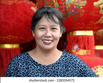 GEORGETOWN, PENANG / MALAYSIA - JAN 10, 2019: Mature Malaysian Chinese woman smiles and poses in front of red-and-gold Chinese lanterns for Chinese New Year, on Jan 10, 2019.