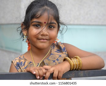 GEORGETOWN, PENANG / MALAYSIA - JAN 30, 2018: Cute little Tamil Malaysian girl with red bindi on her forehead and golden bangles around her left lower arm smiles for the camera, on Jan 30, 2018.