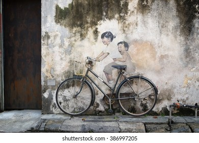 Georgetown, Penang, Malaysia - October 7, 2015: Public street art Name Children on a bicycle painted 3D on the wall that's two little Chinese girls riding bicycle in Georgetown, Penang, Malaysia.