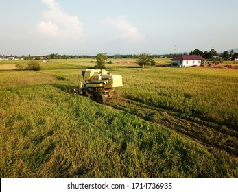 Georgetown, Penang/Malaysia - Feb 29 2020: Aerial view harvester reaping in evening.