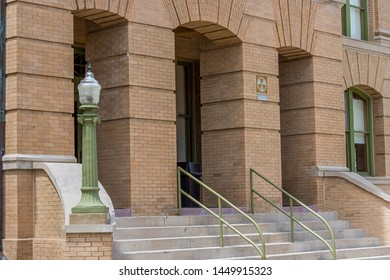 Georgetown, Texas / USA - April 12, 2018: Historic Williamson County Courthouse on Main Street in downtown Georgetown with a fallout shelter sign on the exterior wall and an old green lamp post