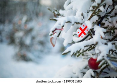 Georgia flag. Christmas background outdoor. Christmas tree covered with snow and decorations and Georgian flag. New Year / Christmas holiday greeting card.