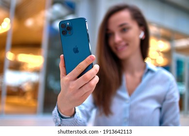 Georgia - January 20, 2021 - Modern casual smart millennial woman using Iphone 12 Pro Max of pacific blue color for video call and remotely chatting online