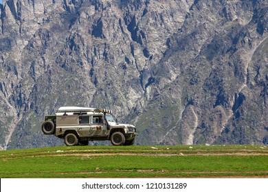 Georgia, Kazbek mountains, 20.08.2018: Vehicle Land Rover Defender is doing off-road trail in Kazbek mountains