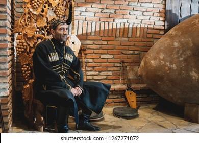 Georgia, Kvevri - November 4, 2018: Man in traditional Georgian costume. Wine factory
