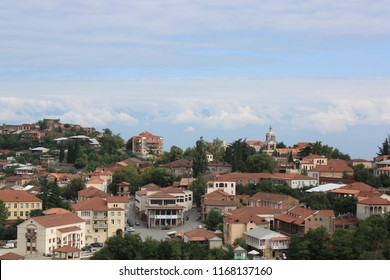 Georgia, Signagi (Sighnaghi). 08.28.2015. View on center of town Signagi with orange roofs, forested mountains, clouds on background. Signagi serves as a popular tourist destination.