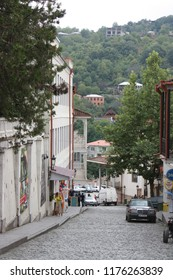 Georgia, Signagi (Sighnaghi). 08.28.2015. View on the street going down of center of medieval town Signagi (Sighnaghi), and forested mountains on background. Kakheti region.
