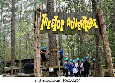 Georgia, USA - March 23,2018 ; The visitors enjoy their treetop adventure, climbing on the wooden block hanging with the rope between tree to tree in Callaway Gardens, Springtime break holiday.