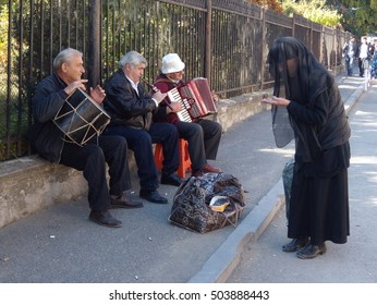 Georgia-Mtskheta.Street musicians playing in celebration Mtskhetoba and collect money, and the woman standing next to them and is going to give them his last penny.