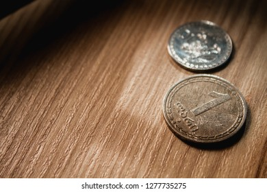 Georgian coins laying on a wooden desk.