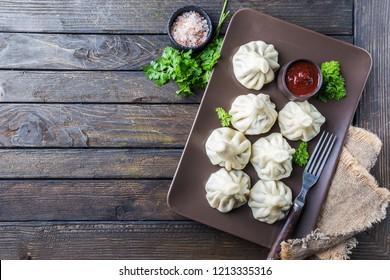 Georgian dumplings Khinkali with meat, greens and tomato spicy sauce Satsebeli, top view