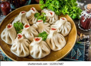 Georgian dumplings Khinkali with meat and red papper, on brown plate
