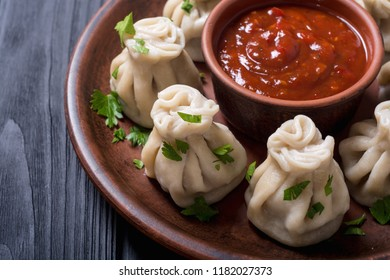 Georgian dumplings khinkali with tomato sauce and parsley