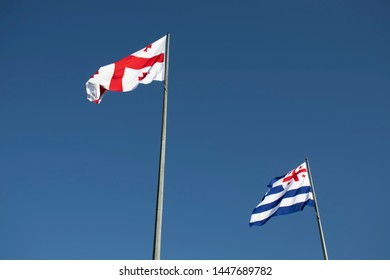 Georgian flag and flag of the Georgian navy against the blue sky. The Georgian flag and the flag of the navy develop in the wind.