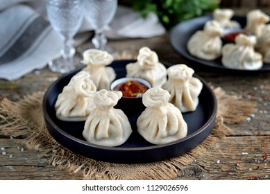 Georgian homemade khinkali (dumplings) with meat and red sauce on an old wooden background. Rustic style.