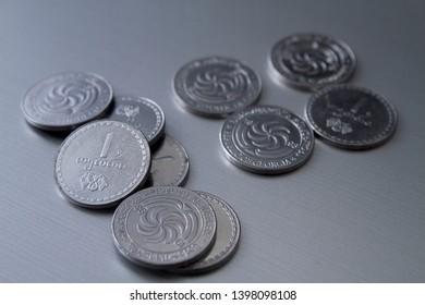Georgian Lari coins on a grey background.