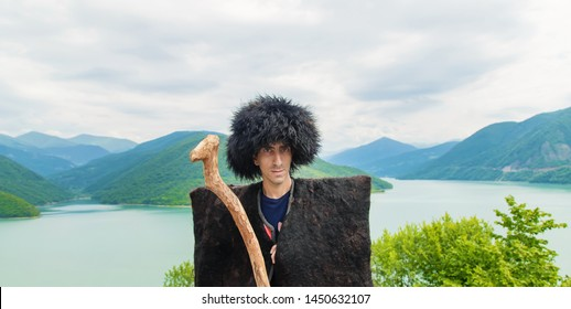 Georgian man in a beech costume on a background of mountains. Selective focus.