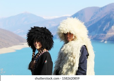 Georgian man  and women  in Georgian national costume with a hat on his head a background of mountains. Selective focus.