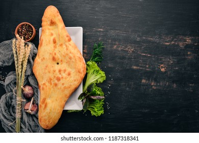 Georgian traditional bread. Georgian cuisine. On the old wooden background. Free space for text. Top view.