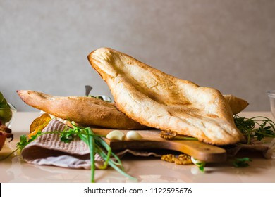 Georgian traditional bread - shoti. Puri made of white wheat flour in round clay oven. This bread is always on table with bunch of greens for Georgian lunch or dinner.