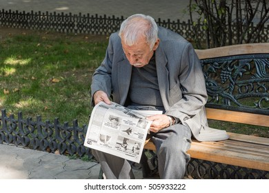 Georgia-Tbilisi.An elderly man reads the world news in the newspaper in the park Rike.10.08.2016.