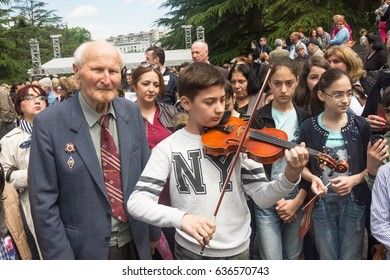 Georgia-Tbilisi.Little boy playing the violin near his grandfather A veteran of the Great Patriotic War On the day of May 9 in the park Vake.5/9/2017.