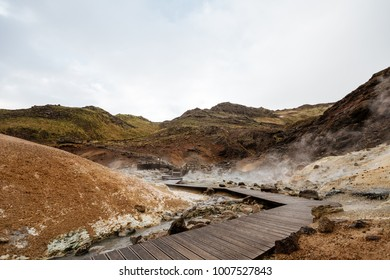 Geothermal area, Iceland. Mud pots are boiling, the ground is multicolored and cracked.