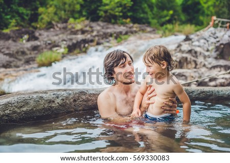 Geothermal spa. Father and son relaxing in hot spring pool against the background of a waterfall. hot springs concept