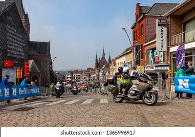 Geraardsbergen, Belgium - April 7, 2019 : Row of official bikes driving on the cobblestone road in Geraardsbergen during Tour of Flanders 2019.