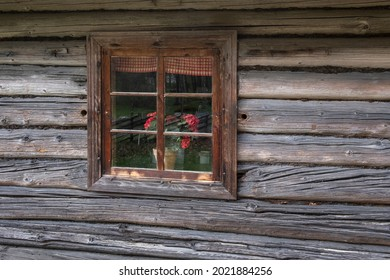 geranium flowers in a window in a strom log house with a straw roof - Shutterstock ID 2021884256