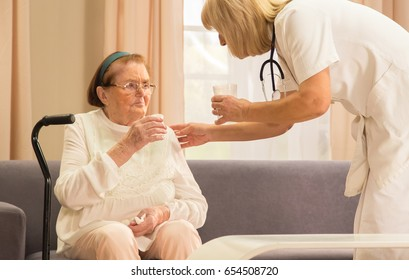 Geriatric clinic sceneof senior female taking therapy with assistance