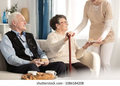 Geriatric couple with arthritis sitting on a couch and being served a piece of cake while waiting for a doctor's appointment at a luxury private clinic