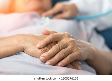Geriatric doctor or geriatrician concept. Hands of elderly seniorParkinson patient and Doctor physician health checking  in hospital examination room or hospice nursing home or wellbeing county.