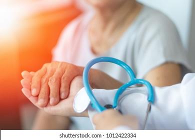 Гериатрический врач или гериатрический концепт.  Врач рука на счастливых пожилых пациентов, чтобы успокоить в больничной комнате обследования или хоспис дома престарелых или благополучия округа.
