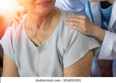 Geriatric doctor or geriatrician concept.  Doctor physician hand on happy elderly senior patient to comfort in hospital examination room or hospice nursing home.