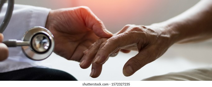 Geriatric doctor or geriatrician concept. Doctor physician hand on happy elderly senior patient to comfort in hospital examination room or hospice nursing home or wellbeing county.